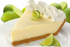Key lime pie on a white plate with limes behind it.