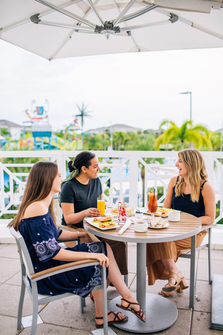 Three women smile as they share food and drinks on the Encore Resort outdoor Clubhouse deck.