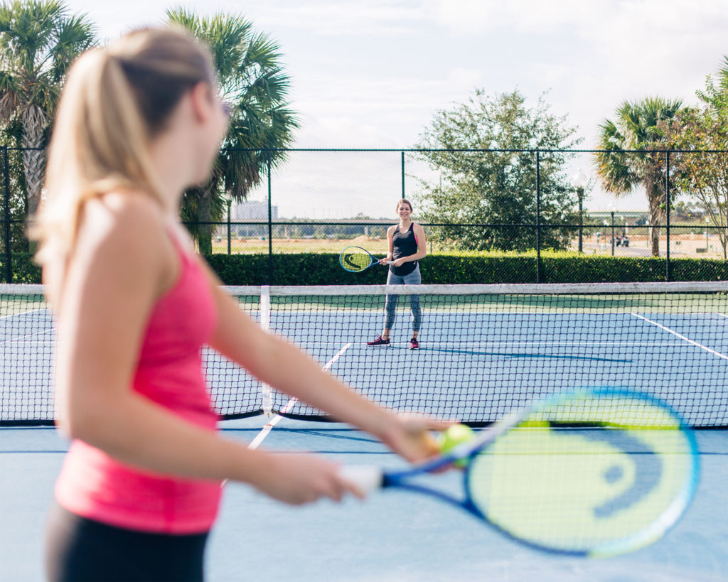 Women playing tennis on the Encore Resort East Side sports facilities.