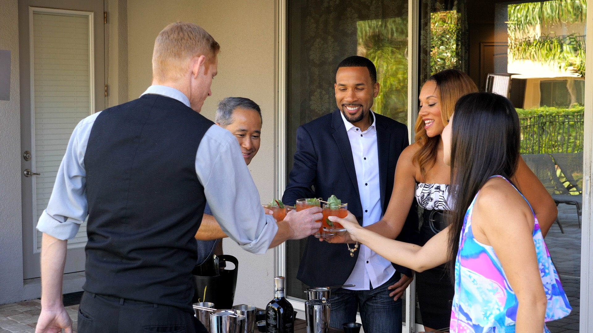 A group clinks glasses in a toast during an Encore Resort in-home bartender experience.